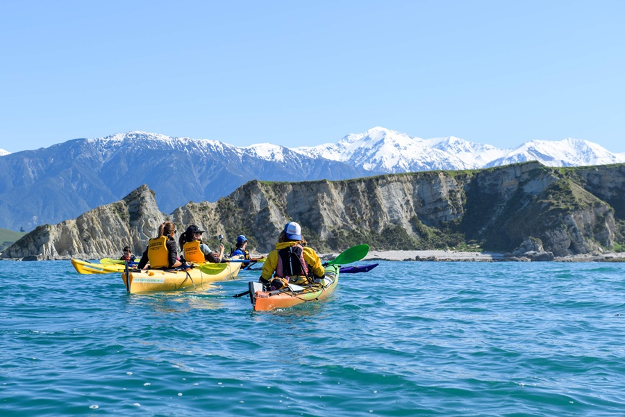 Kaikoura, New Zealand - October 3, 2017 - A group of kayakers paddles in front of snowcapped mountains on October 3, 2017 in Kaikoura, New Zealand.